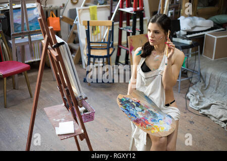 Woman artist painting picture in art studio. Female artist, drawing process. - Stock Photo