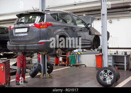 Russia, Izhevsk - October 20, 2018: Automobile workshop. Replacement and wheel alignment on a hydraulic lift. Modern service. - Stock Photo