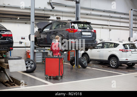 Russia, Izhevsk - October 20, 2018: Car repair in the workshop. Replacement and wheel alignment on a hydraulic lift. Modern service. - Stock Photo