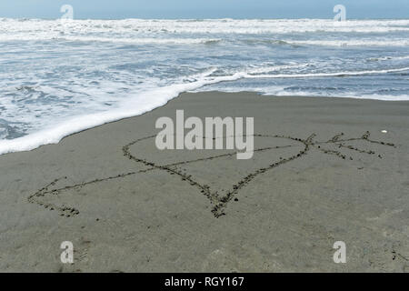 A hand drwan love heart in the sand with an arrow through it - Stock Photo