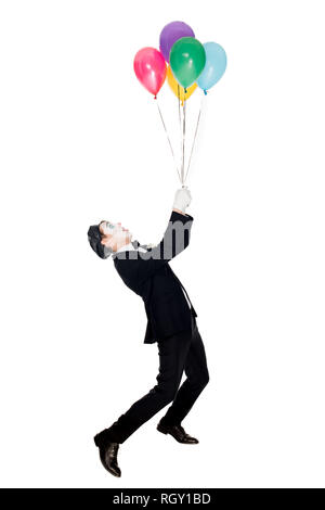 clown in suit and black beret looking at helium balloons isolated on white - Stock Photo