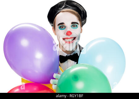 cheerful clown in black beret holding balloons and smiling isolated on white - Stock Photo