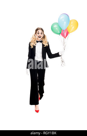 happy female clown in suit holding balloons and smiling isolated on white - Stock Photo