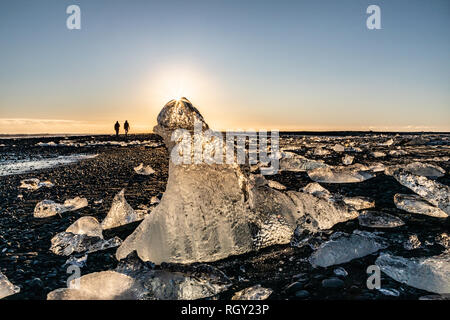 Glacier pieces and sun star with silhouetted couple walking along Iceland's Diamond Beach with black sand along the Ring Road - Stock Photo