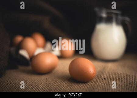 Photo of raw illuminated eggs  in kitchen with jute on dark blurry background Close-up photography of bio chicken eggs in egg box with milk in a ewer  - Stock Photo