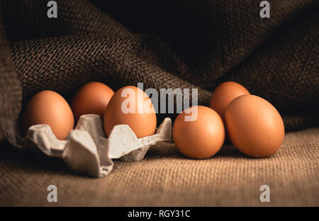 Photo of raw illuminated eggs  in kitchen with jute on dark background. Close-up photography of bio chicken eggs in egg box . - Stock Photo