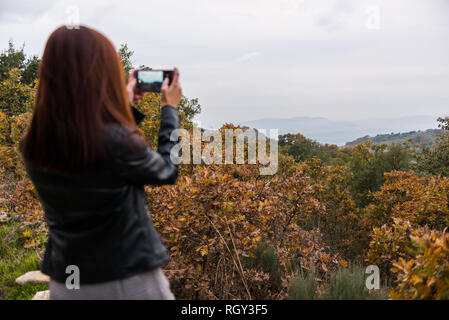 A young red-haired woman takes pictures with her mobile phone in a forest - Stock Photo