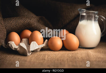 Photo of raw illuminated eggs  in kitchen with jute on dark background. Close-up photography of bio chicken eggs in egg box with milk in a ewer glass. - Stock Photo