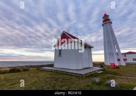 View of a lighthouse on the Atlantic Ocean Coast during a cloudy sunset. Taken at the Historical maritime museum in Rimouski, Quebec, Canada. - Stock Photo