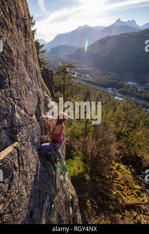 Squamish, BC, Canada - January 15, 2019: Female Rock climber climbing on the edge of the cliff during a sunny winter sunset. - Stock Photo