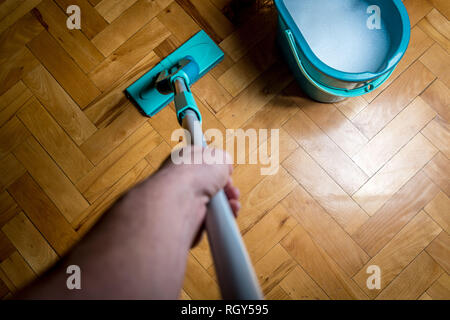 Wiping dirty wooden floor by wet wiper mop, housework. Man cleaning the house. Topview - Stock Photo