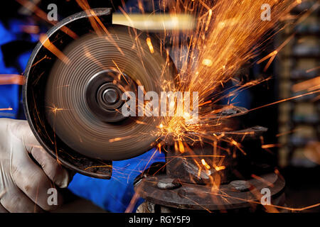 Close-up of a man sawing metal with a hand circular saw,  bright flashes flying in different directions, in the background tools for an auto repair sh - Stock Photo