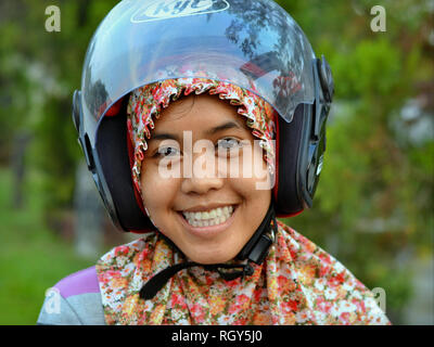 Young Indonesian woman from Kalimantan wears a modern motorcycle crash helmet over her traditional hijab and smiles for the camera. - Stock Photo