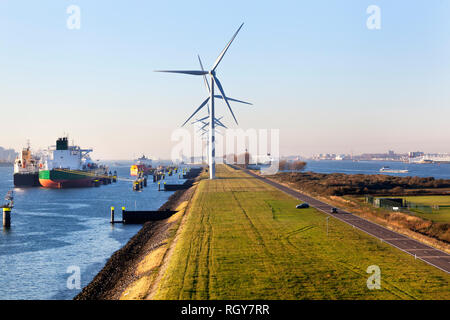 Ships moored in the canal Caland near turbines in the port of Rotterdam - Stock Photo