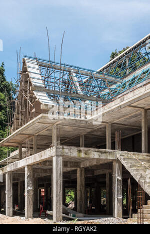 Unfinished temple with the wooden scaffolding in the local town of Thailand. - Stock Photo