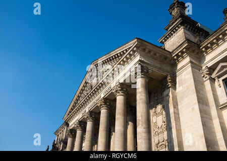 An exterior view of the Reichstag building in Berlin. The historical seat of Germany's parliament since the time of the Holy Roman Empire, it was damaged during Word War II. The ruined building was made safe against the elements and partially refurbished in the 1960s, but no attempt at full restoration was made until after German reunification on 3 October 1990, when it underwent a reconstruction led by architect Norman Foster. After its completion in 1999, it once again became the meeting place of the German parliament: the modern Bundestag. - Stock Photo