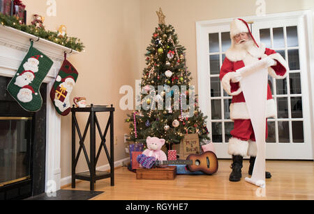 Santa reading his naughty or nice list in a living room decorated for Christmas. - Stock Photo