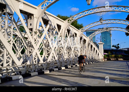 A cyclist on Anderson Bridge in the business district of Singapore, completed in 1910 and spanning the Singapore River; b/g: Marina Bay Sands Hotel - Stock Photo