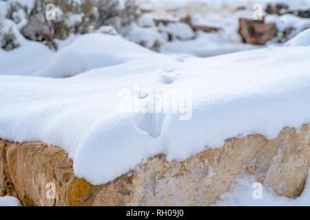 Blanket of snow on a rocky terrain with footprints - Stock Photo