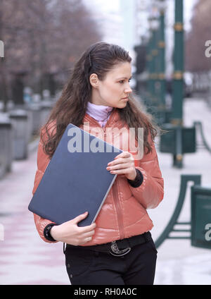 young female student with laptop standing on city street - Stock Photo