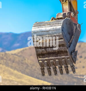 Bucket of an excavator against mountain and sky - Stock Photo
