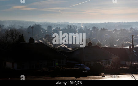Kent, UK. 31st Jan, 2019. The early morning sun shines through a blue crisp sky illuminating the rooftops, the January cold snap hits the south east of England, looking out across the valley in Kent, steam and vapour plumes from chimneys and roofs, the icy tiled roof tops glisten in the low sunshine. 2018 --- Image by Credit: Paul Cunningham/Alamy Live News - Stock Photo