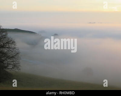 UK Weather: Unique foggy conditions at sunset in North Yorkshire near Easingwold. The recent cold spell continues and in the late afternoon the fog and mist was seen across the local fields and valleys in the Howardian Hills and Vale of York. Credit: credit: Matt Pennington / PennPix/Alamy Live News - Stock Photo