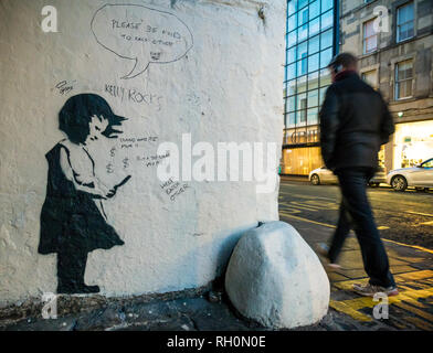 Grindlay Court, Edinburgh, Scotland, United Kingdom, 31st January 2019. Locals spot a new drawing on a wall thought to be a Banksy. In a small alley off Bread Street, a new painting of a young girl looking at a mobile phone appears overnight in the style of Banksy. Graffiti has now been added by others.  Man walking past is oblivious to it. - Stock Photo