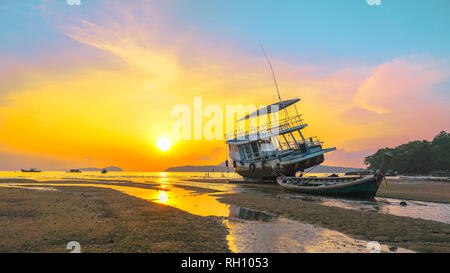 sweet sunrise above fishing boats on the beach. morning light shines up from the edge of the sea. A reflection on fishing boats parked on Rawai beach. - Stock Photo