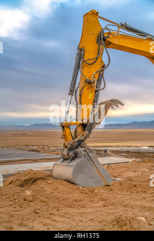 Excavator arm and bucket against mountain and sky - Stock Photo