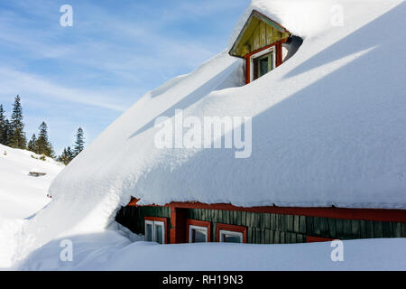 Wooden Cottage Roof Covered with Snow in the Carpathian Mountains - Stock Photo