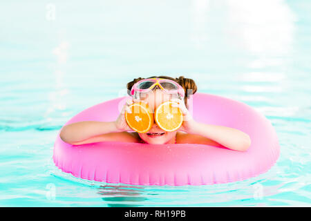 happy child holding half oranges near eyes while  swimming with inflatable ring in swimming pool - Stock Photo