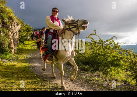 Local people in festive cloths riding back home on horses from a festival celebrating the end of harvest - Stock Photo
