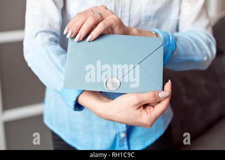 Close-up of a young girl holding a blue rectangular gift envelope with invitations, goods and services card - Stock Photo