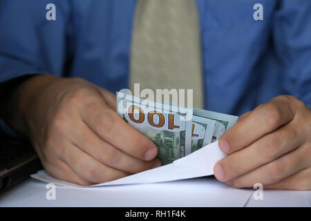 Envelope with dollars in male hands, close-up. Man in business clothes takes the money cash, concept of income, bribe, bonus, wages or savings - Stock Photo