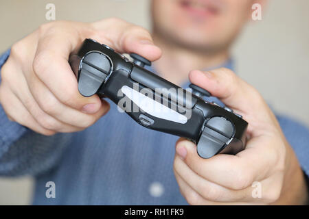 Joystick in male hands close-up, gamer playing video games with gamepad. Gaming addiction concept, home leisure - Stock Photo