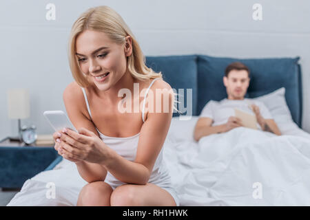 smiling young woman sitting on bed and using smartphone while boyfriend reading book behind
