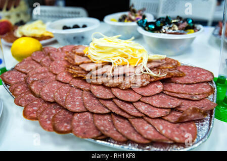 Slices cheese and meat on plate on dinner table - Stock Photo