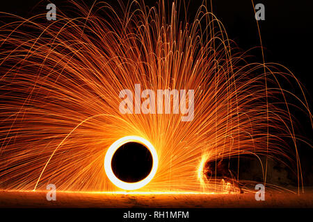 Steel wool photography with umbrella like a protection from burning steel - Stock Photo