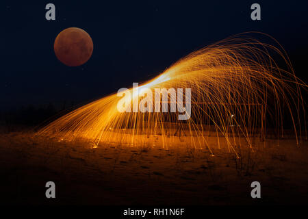 Steel wool photography and moon eclipse at the same time. - Stock Photo