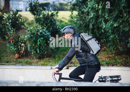 A male bicycle courier cycling in city, delivering packages. Copy space. - Stock Photo