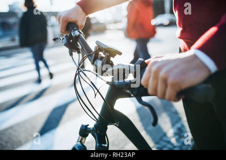A midsection of businessman commuter with electric bicycle traveling to work in city. A close-up. - Stock Photo