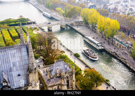 Aerial view from the tower of Notre-Dame de Paris cathedral over the river Seine with tour boats cruising and people strolling on the wharfs. - Stock Photo