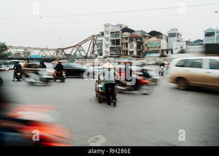 Life of vietnamese vendor in HANOI, VIETNAM. The vendor tried to cross the roads in crazy traffic. - Stock Photo