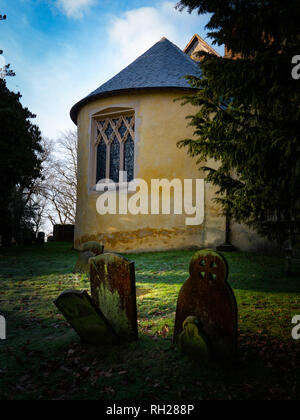 Portrait English village church with cemetery tombstones in early morning sunlight - Stock Photo
