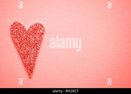 Pink color glittering heart on coral color background with copyspace. - Stock Photo