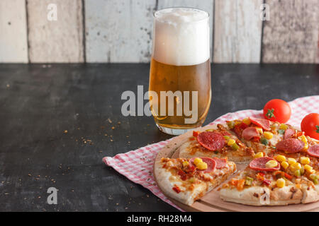 Pizza with corn, sausage, tomatoes on wooden board and light beer with foam in a glass - Stock Photo