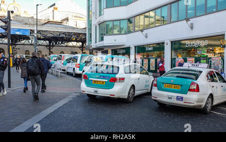 Taxi cabs queue outside Brighton Railway Station in Queens Road Brighton UK  Photograph taken by Simon Dack - Stock Photo