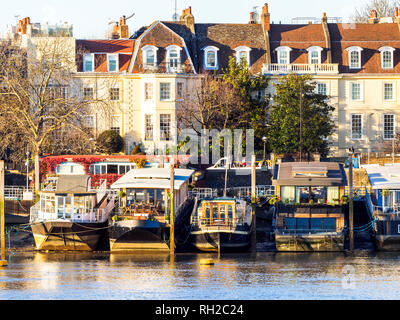 Boats moored at low tide on the Thames river in Chelsea emnbankment - London, England - Stock Photo