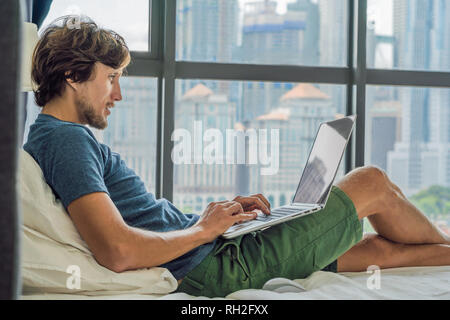 Young man is working on a laptop in his bed on a background of a panoramic window overlooking the skyscrapers. Freelancer, remote work, work from home - Stock Photo